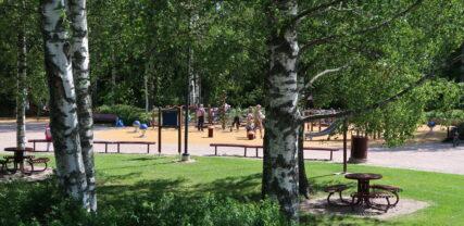 Oleskelualue Thurmaninpuistossa puiden katveessa. Taustalla näkyy leikkipuisto.