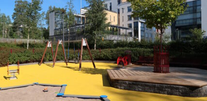 Hiekkalaatikko ja keinu sekä puusta rakennettu istuskelutaso aurinkoisella leikkialueella.