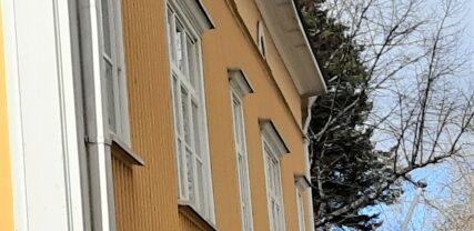 Keltaisen puutalon julkisivu, jossa valkoreunaiset ikkunaruudut.