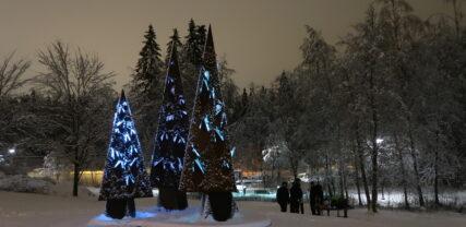 Kolmea kuusta esittävä metallinen taideteos talvella. Kuusten sisältä pilkahtelee valo.