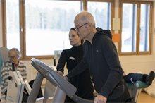 Fysioterapeuttii ohjaa senioria kävelymatolla